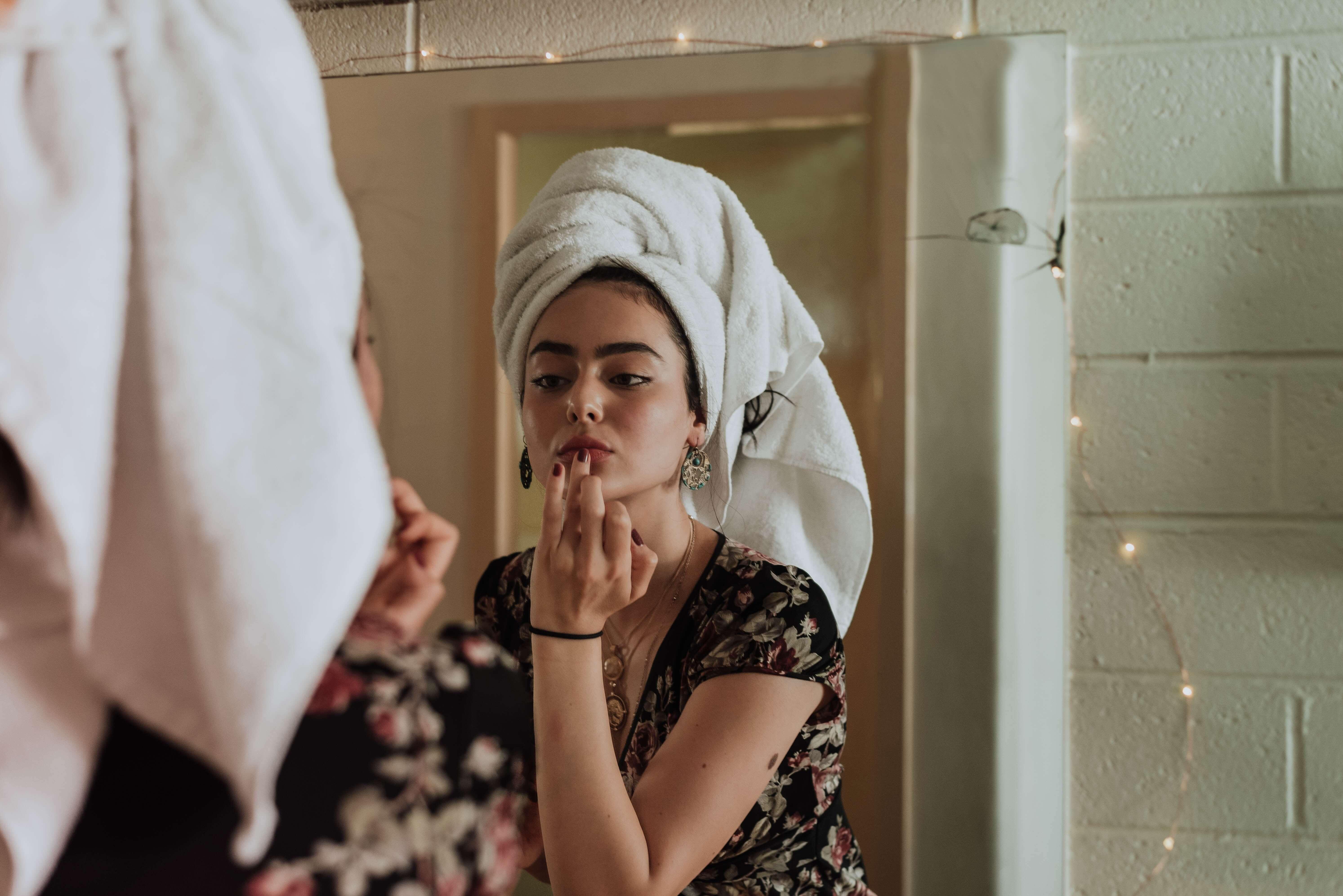 femme qui se maquille devant un miroir